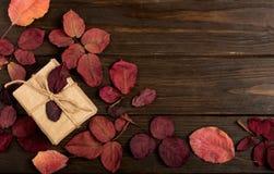 El marco plano de la endecha del carmesí del otoño se va y de las cajas de regalo en una oscuridad imagen de archivo
