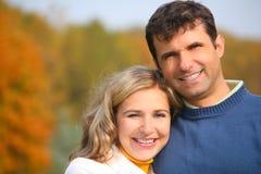 El marido abraza a la esposa en parque del otoño Foto de archivo