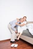 El marido ayuda a la esposa a salir de cama Foto de archivo libre de regalías