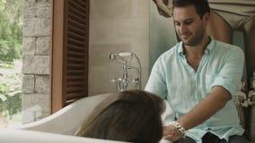 El marido cariñoso regó a su esposa con los pétalos mientras que ella toma el baño en el cuarto con las ventanas panorámicas metrajes