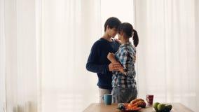 El marido cariñoso y la esposa de la gente joven están bailando en cocina y están besando la risa y la sonrisa disfrutando del mo almacen de video