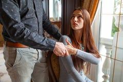 El marido detiene a su esposa al lado de la mano, al lado de la ventana fotos de archivo libres de regalías