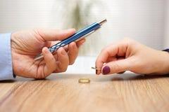 El marido está dando a pluma a los papeles del divorcio de la muestra su esposa anterior a popa imagenes de archivo