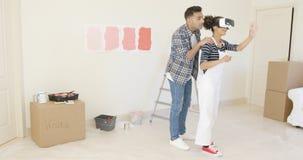 El marido hermoso ayuda a sus guardapolvos que llevan de la esposa imagen de archivo libre de regalías
