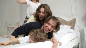 El marido hermoso y la esposa hermosa con dos niños están mintiendo en la cama blanca Los padres divertidos con sonrisas encantad almacen de metraje de vídeo
