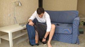 El marido que el alcohólico se sienta en el sofá sale de un alcohol de la maleta un divorcio almacen de metraje de vídeo
