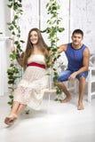 El marido rueda a su esposa en un oscilación Foto de archivo libre de regalías