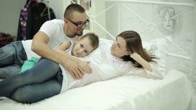 El marido y el hijo que frotan ligeramente el vientre de la madre metrajes