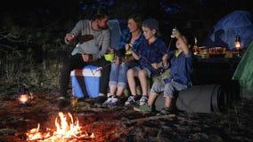 El marido y la esposa con los niños pone el céfiro para ensartar cerca de hoguera en el arbolado, familia comunica metrajes