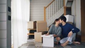 El marido y la esposa de la gente joven son que hablan y que besan la sentada en piso de la nueva casa cerca de escalera y de sue metrajes