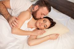 El marido y la esposa despiertan por la mañana en un amor del dormitorio fotografía de archivo libre de regalías