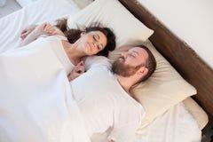 El marido y la esposa despiertan por la mañana en un amor del dormitorio imagen de archivo libre de regalías