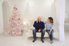 El marido y la esposa felices utilizan smartphone para felicitar a parientes Foto de archivo