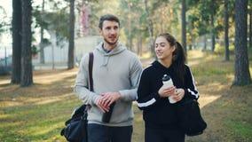 El marido y la esposa jovenes de los pares están caminando en parque y los bolsos y las botellas de agua que llevan que hablan, i almacen de video