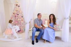 El marido y la esposa se dan los regalos de la Navidad en spaci brillante Fotos de archivo libres de regalías