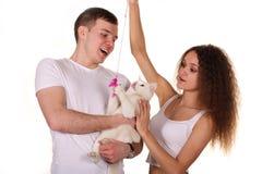 El marido y la esposa sostienen el gato aislado en el fondo blanco Foto de archivo