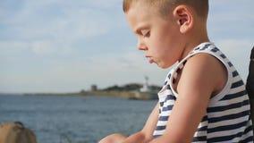 El marinero que lleva del niño pequeño feliz raya la camisa que juega en fondo del cielo y del mar almacen de metraje de vídeo