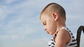 El marinero que lleva del niño pequeño lindo raya la camisa en fondo del cielo almacen de metraje de vídeo