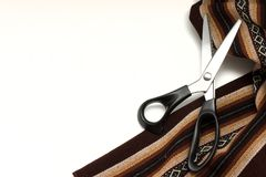 El marrón grueso modeló la tela y las tijeras de costura aisladas en el fondo blanco Copie el espacio Imágenes de archivo libres de regalías