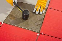 El martillo de goma instala los azulejos de cristal Fotos de archivo libres de regalías