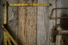 El martillo de la cinta métrica y vio en la madera vieja rústica Foto de archivo