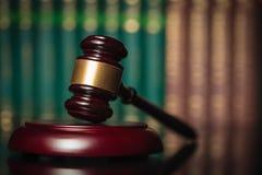 El martillo del juez delante de la fila de los libros de ley Foto de archivo libre de regalías