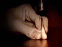 El martillo golpeó el clavo fotografía de archivo libre de regalías
