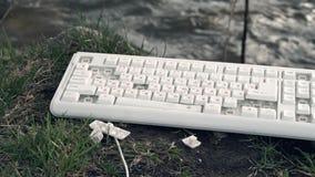 El martillo rompe un teclado de ordenador Teclado de ordenador quebrado en naturaleza El concepto de impacto adverso del ` s de l almacen de metraje de vídeo