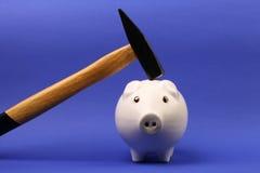El martillo se aumenta sobre una hucha rosada blanca al revés en fondo azul Imagen de archivo libre de regalías