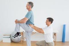 El masaje del terapeuta sirve más de espalda en hospital del gimnasio foto de archivo