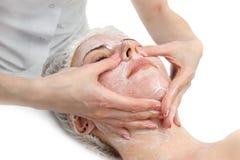 El masaje facial con friega la máscara Imagenes de archivo