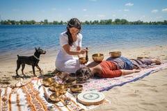 El masaje sano de recepción femenino hermoso de la energía con el canto rueda en una orilla del río fotos de archivo