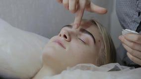 El masajista aplica la crema facial del masaje a una chica joven en un salón de belleza almacen de video