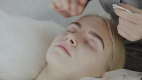 El masajista aplica la crema facial del masaje a una chica joven en un salón de belleza almacen de metraje de vídeo