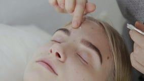 El masajista aplica la crema facial del masaje a una chica joven en un salón de belleza metrajes