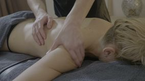 El masajista de sexo masculino experimentado hace un masaje terapéutico de los hombros a un paciente rubio femenino grueso en un  almacen de metraje de vídeo