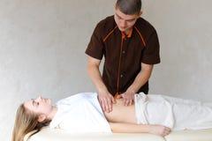 El masajista de sexo masculino fuerte con los movimientos apacibles de la mano amasa el vientre de c Foto de archivo