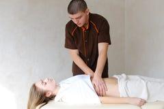 El masajista de sexo masculino fuerte con los movimientos apacibles de la mano amasa el vientre de c Fotografía de archivo