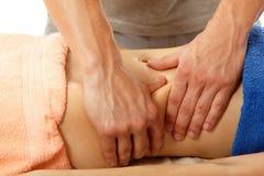 El masajista hace masaje del vientre a la mujer joven aislada en blanco Foto de archivo libre de regalías