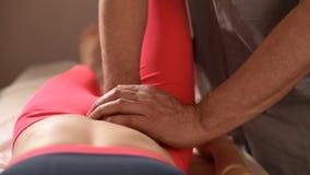 El masajista visceral manual de sexo masculino del terapeuta trata a un paciente femenino joven El corregir externo del ?tero metrajes