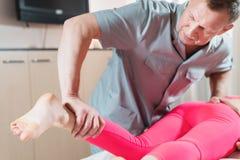 El masajista visceral manual de sexo masculino del terapeuta trata a un paciente femenino joven Trabajo con las nalgas del m?s de imágenes de archivo libres de regalías