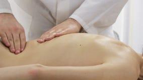 El massageit del doctor da masajes a más de espalda de una chica joven almacen de video