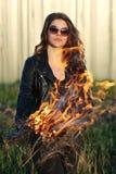 El matón de la muchacha que se coloca en una chaqueta negra es un fuego en sus manos al aire libre Imagenes de archivo