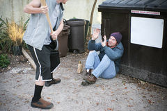 El matón amenaza al hombre sin hogar Imagen de archivo libre de regalías