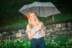 El mayor de High School secundaria presenta con el paraguas para los retratos en un lluvioso Foto de archivo libre de regalías