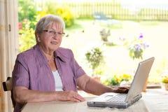 El mayor femenino está utilizando el ordenador Fotos de archivo libres de regalías