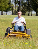 Hombre mayor en el cortacésped cero de la vuelta en césped Foto de archivo libre de regalías