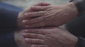 El mayor sirve las manos que alcanzan hacia fuera Mujer que pone sus manos en manos de los varones Relaciones de familia almacen de video