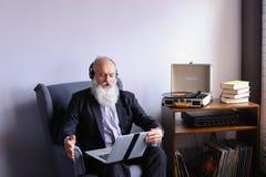 El mayor trabaja en el ordenador y disfruta de música en los auriculares a través Imagen de archivo libre de regalías
