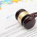 El mazo del juez de madera sobre los documentos y el mapa del mundo - tiro ascendente cercano del acuerdo Fotografía de archivo libre de regalías